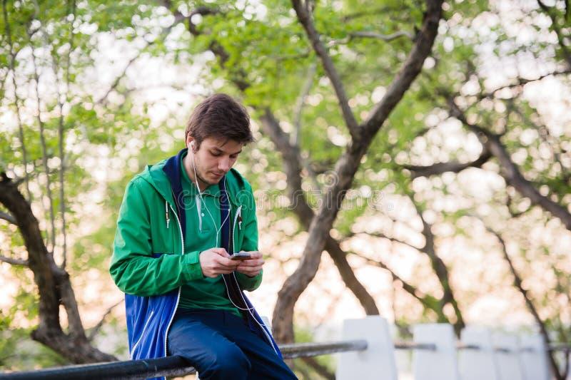 Νέα συνεδρίαση ανδρών σπουδαστών στο πάρκο στο ηλιοβασίλεμα σχετικά με το κινητό τηλέφωνο που ακούει τη μουσική Μαλακό ελαφρύ και στοκ φωτογραφίες