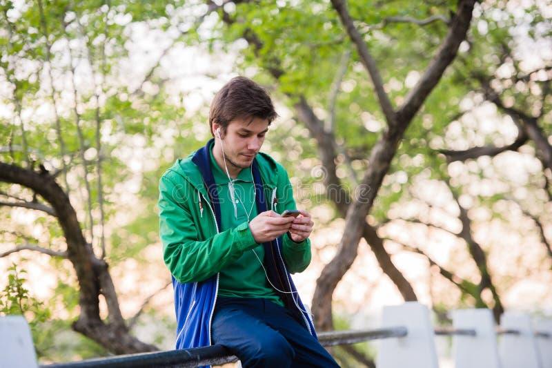 Νέα συνεδρίαση ανδρών σπουδαστών στο πάρκο στο ηλιοβασίλεμα σχετικά με το κινητό τηλέφωνο που ακούει τη μουσική Μαλακό ελαφρύ και στοκ εικόνες με δικαίωμα ελεύθερης χρήσης