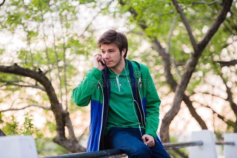 Νέα συνεδρίαση ανδρών σπουδαστών στο πάρκο στο ηλιοβασίλεμα σχετικά με το κινητό τηλέφωνο που ακούει τη μουσική Μαλακό ελαφρύ και στοκ φωτογραφία με δικαίωμα ελεύθερης χρήσης