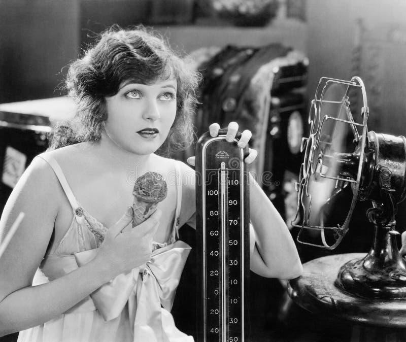 Νέα συνεδρίαση γυναικών δίπλα σε έναν ανεμιστήρα και ένα θερμόμετρο που φαίνονται καυτούς και που τρώνε ένα παγωτό (όλα τα πρόσωπ στοκ εικόνα με δικαίωμα ελεύθερης χρήσης