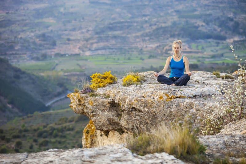 Νέα συνεδρίαση γυναικών σε έναν βράχο στη θέση asana στοκ εικόνες