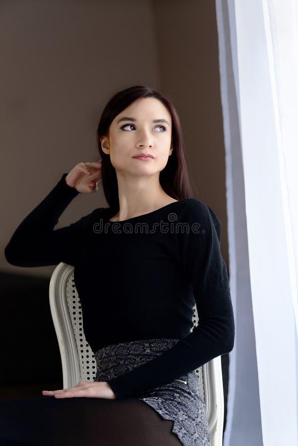 Νέα συνεδρίαση γυναικών στην ντεμοντέ καρέκλα κοντά στο παράθυρο στοκ φωτογραφίες