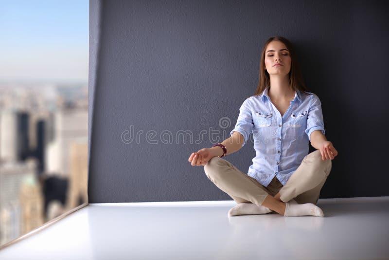 Νέα συνεδρίαση γυναικών στο πάτωμα κοντά στον τοίχο, να κάνει στοκ εικόνες με δικαίωμα ελεύθερης χρήσης
