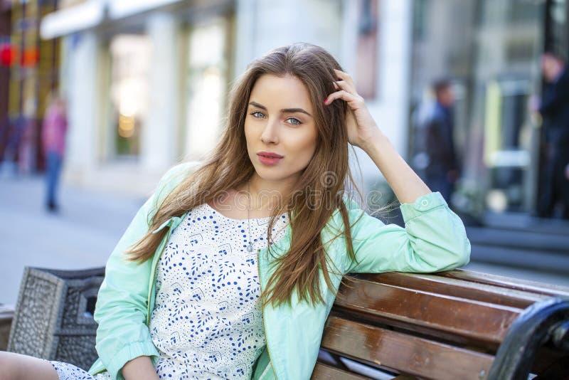 Νέα συνεδρίαση γυναικών brunette στον πάγκο στη θερινή οδό στοκ εικόνα