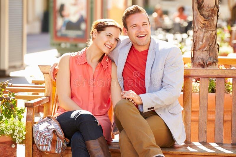 Νέα συνεδρίαση ζεύγους στο κάθισμα στη λεωφόρο από κοινού στοκ φωτογραφίες