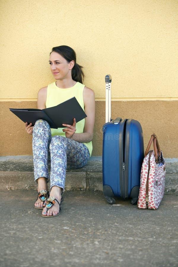 Νέα συνεδρίαση τουριστών γυναικών με τις αποσκευές και ένα φυλλάδιο ι ταξιδιού στοκ εικόνες