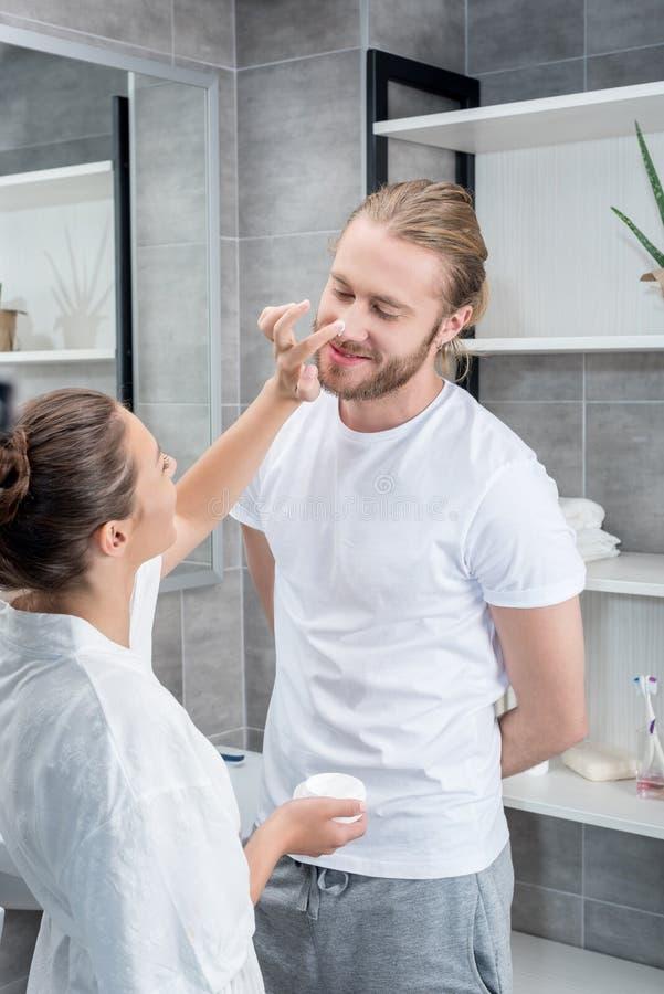 Νέα σύζυγος που εφαρμόζει την κρέμα προσώπου στο μάγουλο συζύγων στο λουτρό στοκ εικόνες