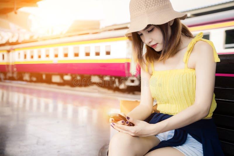 Νέα ταξιδιωτική γυναίκα που κρατά το κινητό τηλεφωνικό διαθέσιμο χέρι περιμένοντας στην πλατφόρμα στο σιδηροδρομικό σταθμό που πε στοκ εικόνα με δικαίωμα ελεύθερης χρήσης