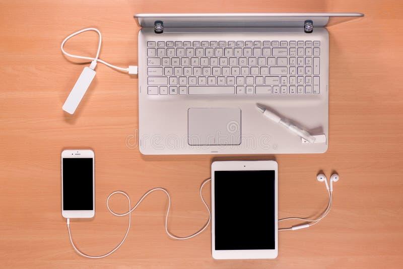 Νέα τεχνολογία στο γραφείο: ανοικτό lap-top με τη χρέωση της τράπεζας δύναμης, του κινητού τηλεφώνου, της ταμπλέτας, των ακουστικ στοκ εικόνες με δικαίωμα ελεύθερης χρήσης