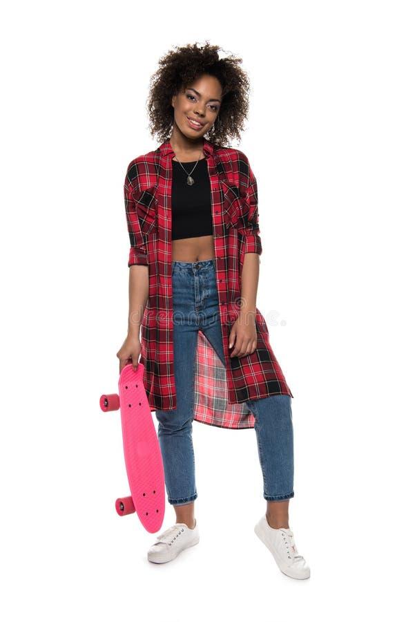 Νέα τοποθέτηση γυναικών αφροαμερικάνων με skateboard και χαμόγελο στη κάμερα που απομονώνεται στο λευκό στοκ φωτογραφίες