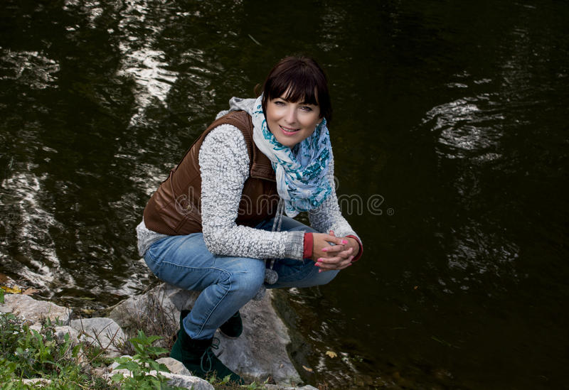 Νέα τοποθέτηση γυναικών κοντά στη λίμνη βραδιού στοκ φωτογραφία με δικαίωμα ελεύθερης χρήσης