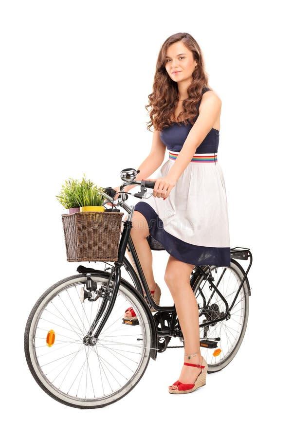 Νέα τοποθέτηση γυναικών που κάθεται σε ένα μαύρο ποδήλατο στοκ εικόνες