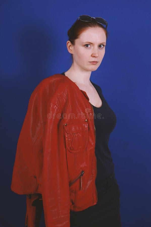 Νέα τοποθέτηση γυναικών στο εκλεκτής ποιότητας σακάκι δέρματος μόδας κόκκινο στοκ φωτογραφία