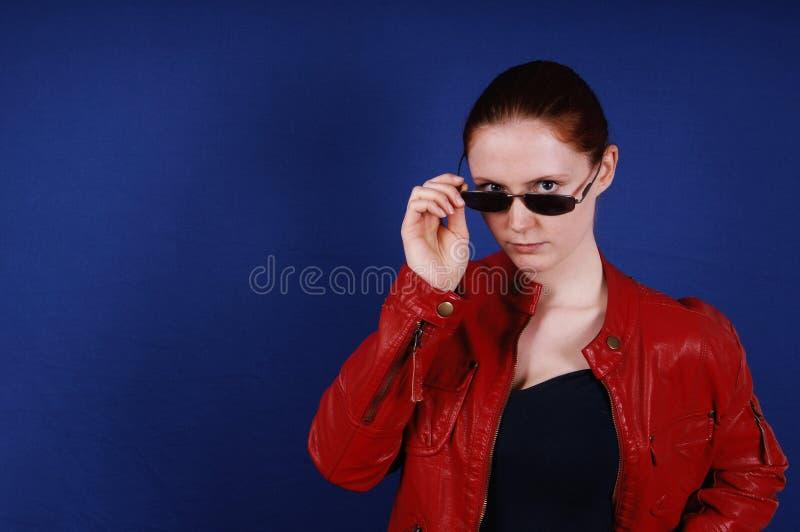 Νέα τοποθέτηση γυναικών στο εκλεκτής ποιότητας σακάκι και τα γυαλιά ηλίου δέρματος μόδας κόκκινα στοκ φωτογραφίες