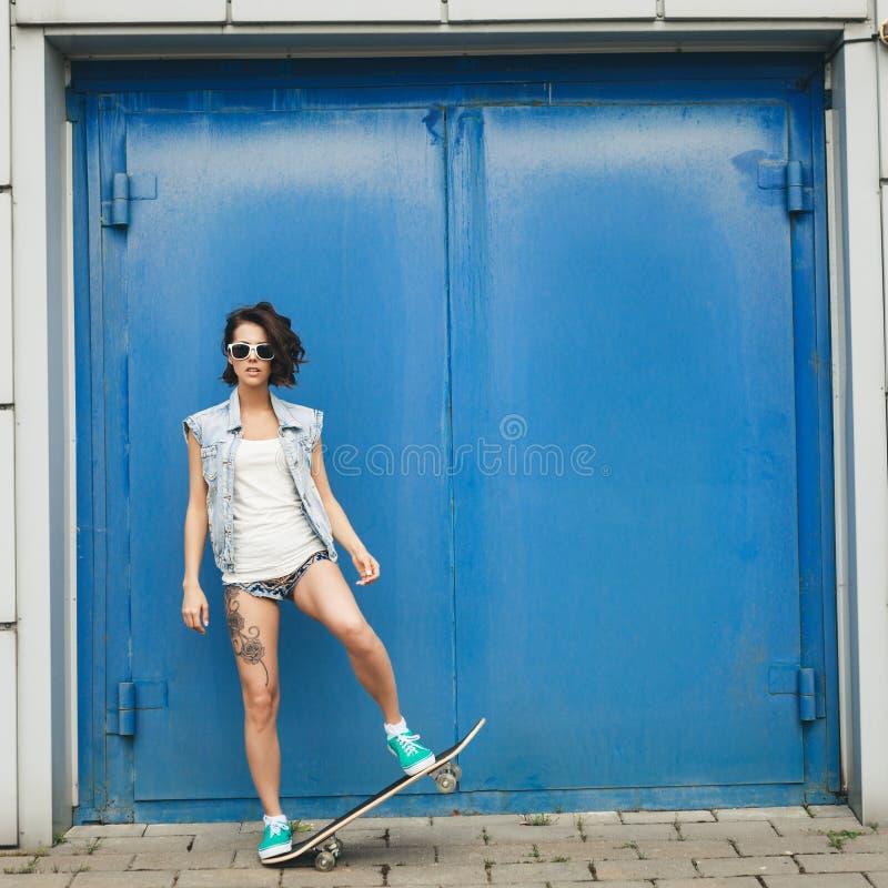 Νέα τοποθέτηση γυναικών brunette με skateboard στοκ φωτογραφία
