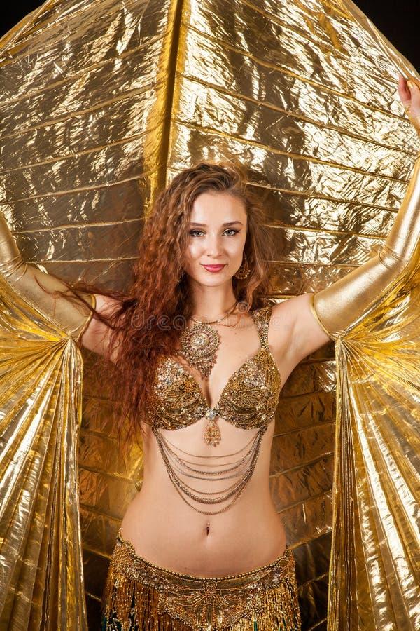 Νέα τοποθέτηση χορευτών κοιλιών στο χρυσό κοστούμι με Isis τα φτερά στοκ φωτογραφία με δικαίωμα ελεύθερης χρήσης