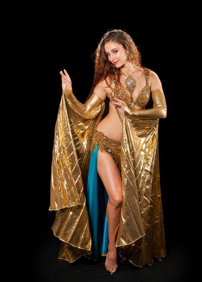 Νέα τοποθέτηση χορευτών κοιλιών στο χρυσό κοστούμι με Isis τα φτερά στοκ φωτογραφία