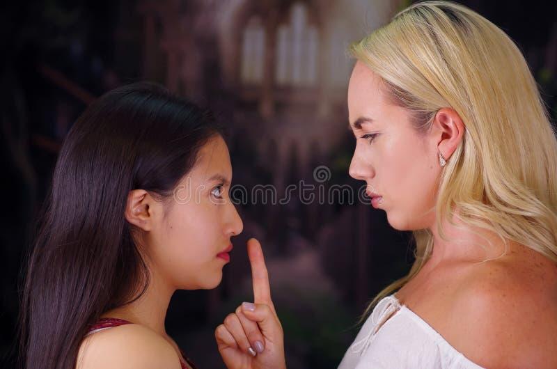 Νέα τρελλή αμερικανική ξανθή γυναίκα, που βάζει το δάχτυλό της στο στόμα μιας ξένης γυναίκας, που προσποιείται να την κρατήσει στ στοκ φωτογραφία