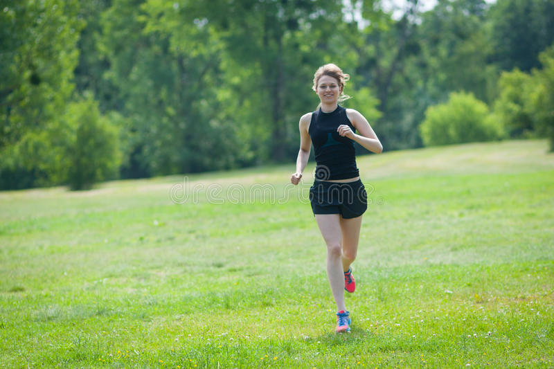 Νέα τρεξίματα γυναικών στο πάρκο στοκ εικόνες