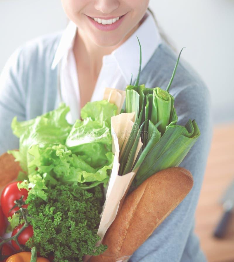 Νέα τσάντα αγορών παντοπωλείων εκμετάλλευσης γυναικών με τα λαχανικά Στάση στην κουζίνα στοκ φωτογραφία με δικαίωμα ελεύθερης χρήσης