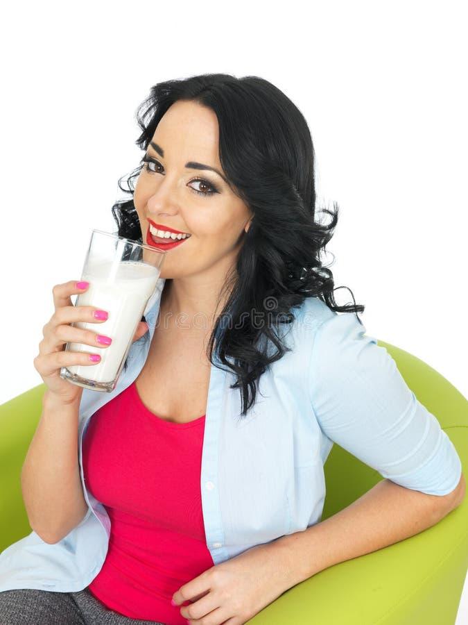 Νέα υγιής χαμογελώντας γυναίκα που πίνει ένα γυαλί της αναζωογόνησης του γάλακτος στοκ εικόνες με δικαίωμα ελεύθερης χρήσης