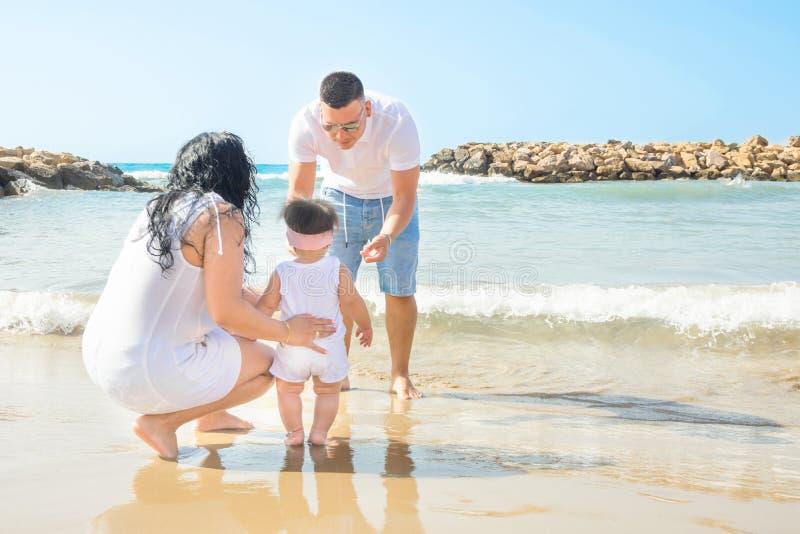 Νέα υποστήριξη λαβής γονέων χαριτωμένη λίγη κόρη κοριτσιών μικρών παιδιών μωρών που μαθαίνει να περπατά Μπλε φως του ήλιου θάλασσ στοκ εικόνες