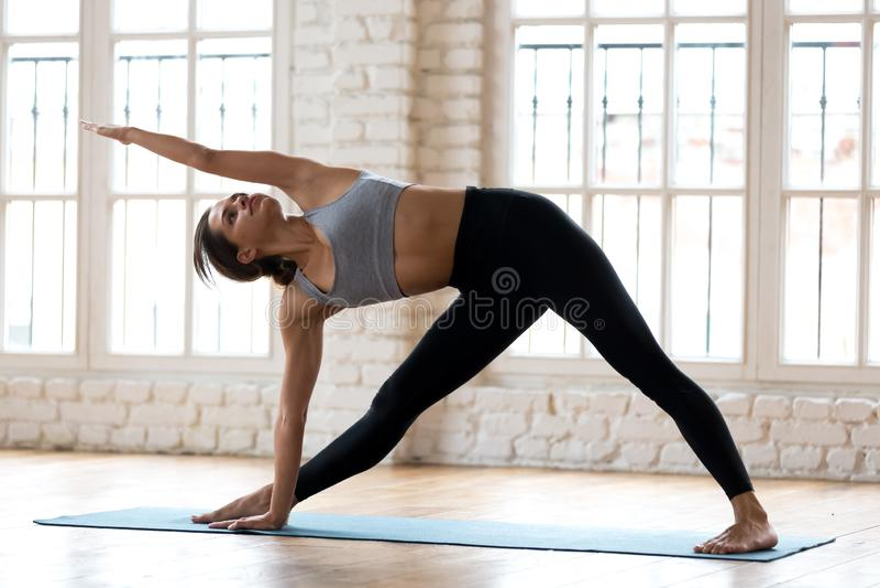 Νέα φίλαθλη ελκυστική γιόγκα άσκησης γυναικών, που κάνει Utthita τρι στοκ εικόνες