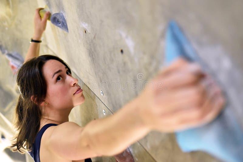 Νέα, φίλαθλη όμορφη γυναίκα που αναρριχείται επάνω σε έναν τοίχο σε ένα bouldering εκτάριο στοκ φωτογραφία