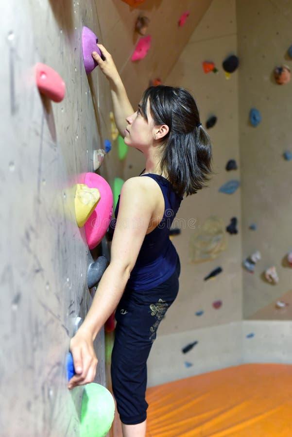 Νέα, φίλαθλη όμορφη γυναίκα που αναρριχείται επάνω σε έναν τοίχο σε ένα bouldering εκτάριο στοκ φωτογραφία με δικαίωμα ελεύθερης χρήσης