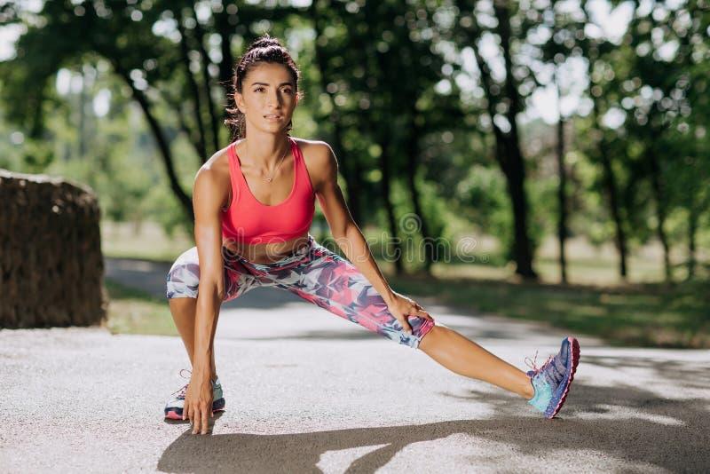 Νέα φίλαθλος που τεντώνει και που προετοιμάζεται να τρέξει Αθλητικός τρόπος ζωής στοκ φωτογραφία