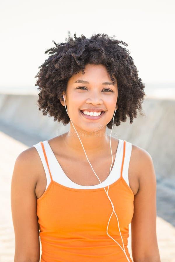 Νέα φίλαθλη γυναίκα που απολαμβάνει τη μουσική μέσω των ακουστικών στοκ φωτογραφίες με δικαίωμα ελεύθερης χρήσης