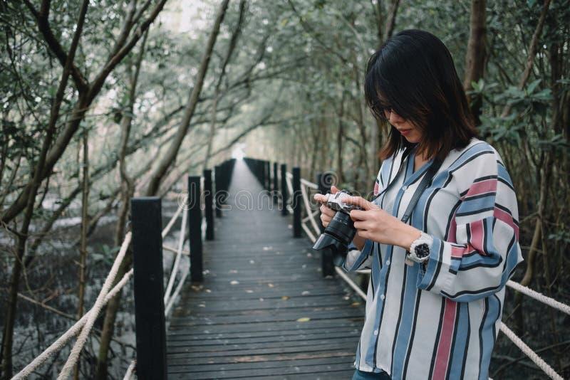 Νέα φωτογραφία γυναικών με τη κάμερα, ξύλινη γέφυρα και όμορφος στοκ φωτογραφία με δικαίωμα ελεύθερης χρήσης