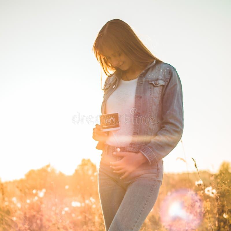 Νέα φωτογραφία υπερήχου εκμετάλλευσης εγκύων γυναικών στο ηλιοβασίλεμα και το αγκάλιασμα της κοιλιάς της 4 εγκυμοσύνη μήνα Έννοια στοκ φωτογραφία με δικαίωμα ελεύθερης χρήσης