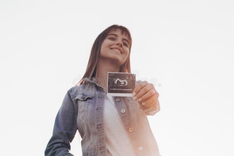 Νέα φωτογραφία υπερήχου εκμετάλλευσης εγκύων γυναικών στο ηλιοβασίλεμα και το αγκάλιασμα της κοιλιάς της 4 εγκυμοσύνη μήνα Έννοια στοκ εικόνα με δικαίωμα ελεύθερης χρήσης