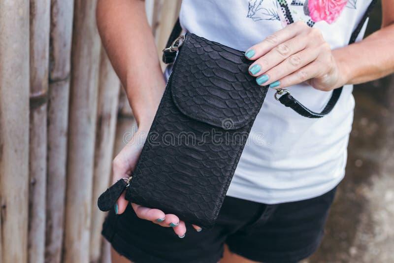 Νέα χέρια γυναικών με τη μοντέρνη τσάντα πολυτέλειας snakeskin python υπαίθρια Νησί του Μπαλί στοκ εικόνα με δικαίωμα ελεύθερης χρήσης