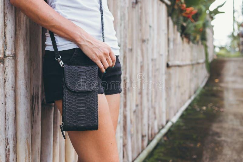 Νέα χέρια γυναικών με τη μοντέρνη τσάντα πολυτέλειας snakeskin python υπαίθρια Νησί του Μπαλί στοκ εικόνες
