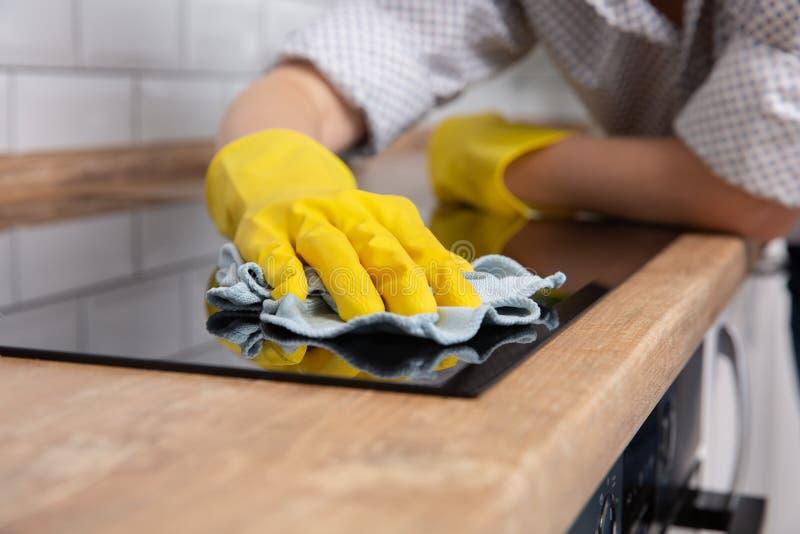 Νέα χέρια γυναικών που καθαρίζουν σύγχρονο μαύρο hob επαγωγής από ένα κουρέλι, οικιακά στοκ εικόνες