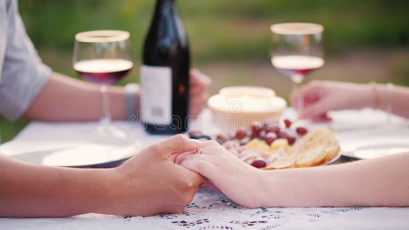Νέα χέρια εκμετάλλευσης ζευγών, ρομαντικό γεύμα με το κρασί στοκ εικόνα με δικαίωμα ελεύθερης χρήσης