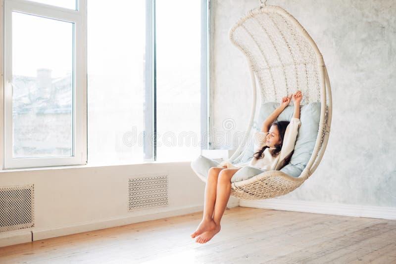 Νέα χαλάρωση έφηβη στην άνετη κρεμώντας καρέκλα κοντά στο παράθυρο στο σπίτι Συνεδρίαση παιδιών στην καρέκλα και κατάψυξη έξω στοκ φωτογραφία