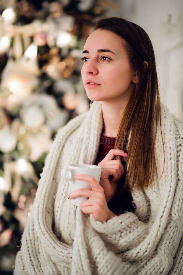 Νέα χαλάρωση γυναικών με μια κούπα του καφέ όπως αγκαλιάζει επάνω στο θερμό κάλυμμα στο αρχαίο κομό Οι προσοχές της ιδιαίτερες κα στοκ εικόνα