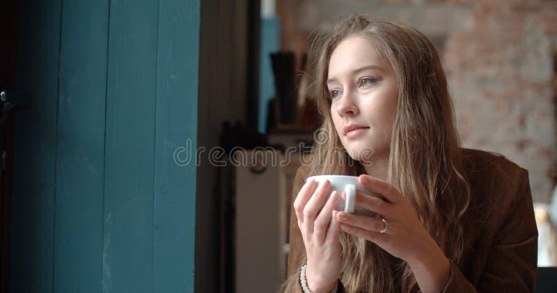 Νέα χαλάρωση γυναικών με το φλιτζάνι του καφέ στο άνετο εστιατόριο στοκ εικόνα με δικαίωμα ελεύθερης χρήσης
