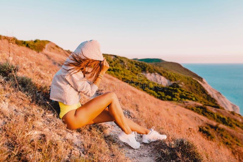 Νέα χαλάρωση γυναικών στη φύση στο θερμό ηλιοβασίλεμα Κορίτσι ικανότητας στα βουνά στοκ φωτογραφίες