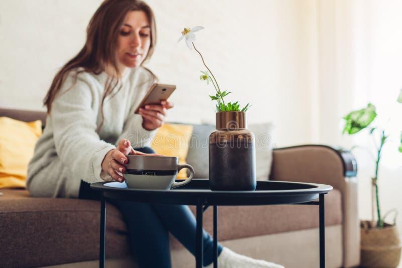 Νέα χαλάρωση γυναικών στο καθιστικό χρησιμοποιώντας το smartphone και πίνοντας τον καφέ E στοκ εικόνες