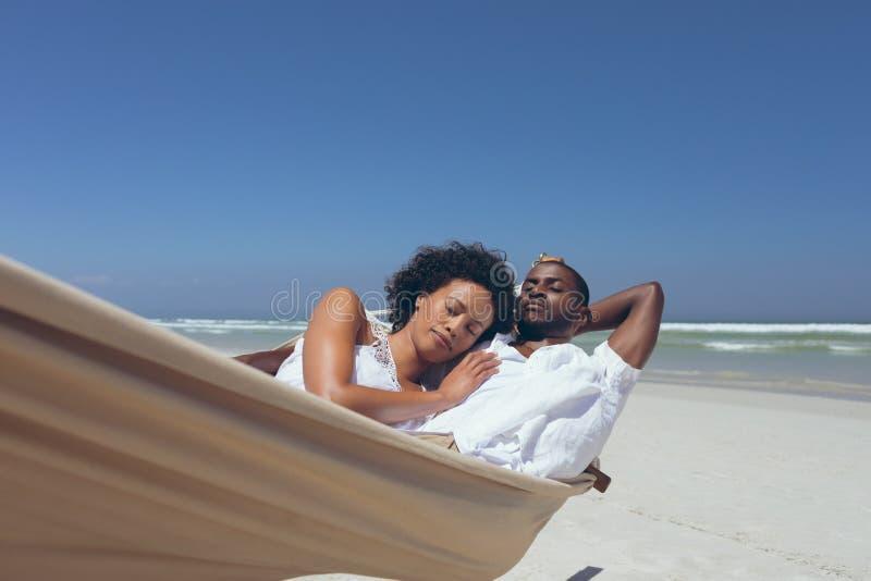 Νέα χαλάρωση ζευγών στην αιώρα στην παραλία στοκ φωτογραφίες με δικαίωμα ελεύθερης χρήσης