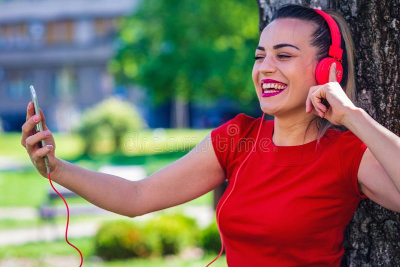 Νέα χαμογελώντας γυναίκα που κάνει την τηλεοπτική κλήση μέσω του smartphone και του headpho στοκ φωτογραφία με δικαίωμα ελεύθερης χρήσης