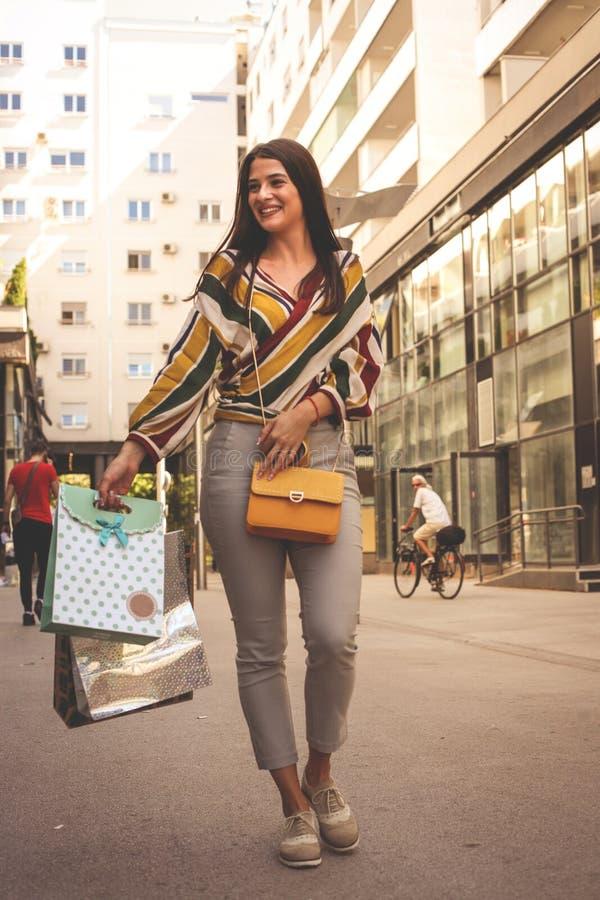 Νέα χαμογελώντας γυναίκα που περπατά στην οδό με τις τσάντες αγορών στοκ εικόνες με δικαίωμα ελεύθερης χρήσης