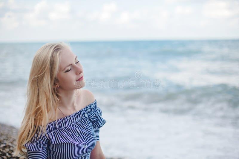 Νέα χαμογελώντας γυναίκα στη θάλασσα στοκ φωτογραφία
