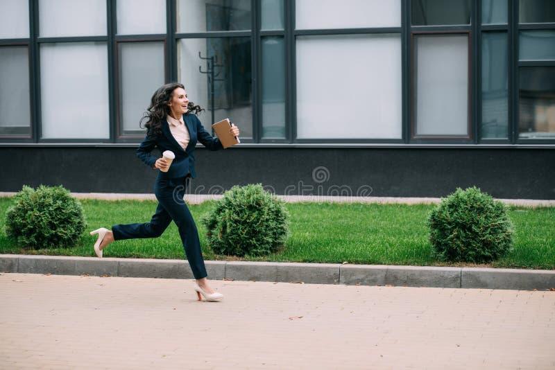 νέα χαμογελώντας επιχειρηματίας που τρέχει στην εργασία με τον καφέ στοκ φωτογραφίες