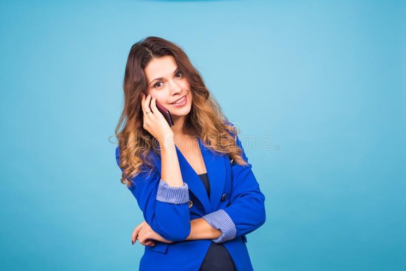 Νέα χαμογελώντας επιχειρησιακή γυναίκα που μιλά το OH το τηλέφωνο, στο μπλε υπόβαθρο στοκ εικόνα με δικαίωμα ελεύθερης χρήσης