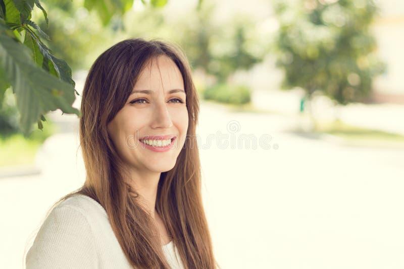 Νέα χαμογελώντας γυναίκα με τα υγιή δόντια στην ηλιόλουστη θερινή ημέρα στοκ εικόνα